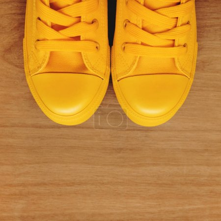 Photo for Stylish yellow sneakers on wooden background from above with copy space - Royalty Free Image