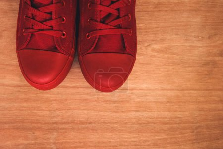 Photo for Stylish red sneakers on wooden background from above with copy space - Royalty Free Image