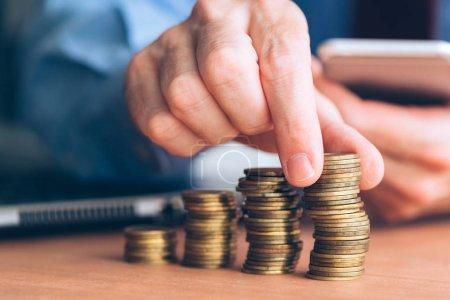 Photo pour Finances et budgétisation, homme d'affaires empilant des pièces sur le bureau - image libre de droit