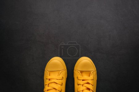 Photo for Stylish yellow sneakers on dark background with copy space, top view - Royalty Free Image