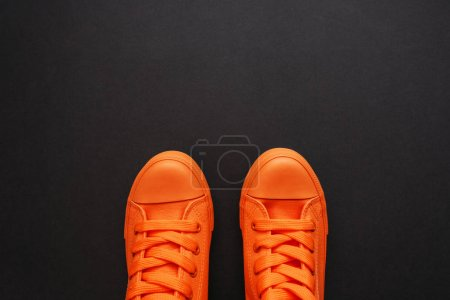 Photo for Stylish orange sneakers on dark background with copy space, top view - Royalty Free Image