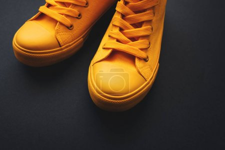 Photo for Stylish yellow sneakers on dark background with copy space - Royalty Free Image
