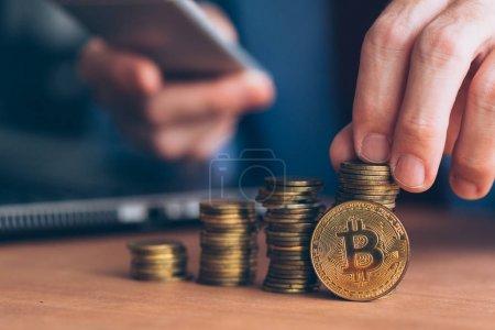 Photo pour Bitcoin cryptocurrency commerçant, homme d'affaires à l'aide de la technologie moderne électronique au commerce avec l'argent de crypto, empilés au premier plan, les pièces de monnaie et dus, homme d'affaires en arrière-plan - image libre de droit