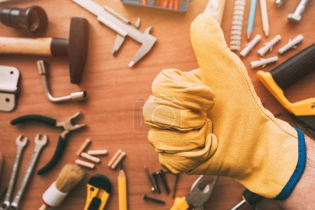 Photo for Maintenance handyman gesturing thumb up approval hand sign over the work desk with DIY tools, top view - Royalty Free Image