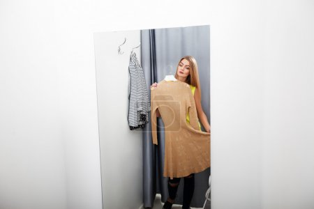 Woman with dress in checkroom