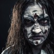 Portrait of horror zombie woman with bloody face a...