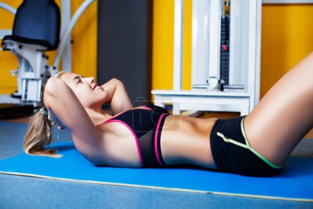 Young happy girl exercising abs