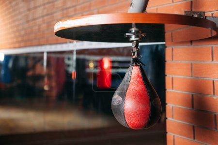 Photo pour Sac de boxe noir et rouge. Salle de sport sur le fond. Thème de la boxe - image libre de droit