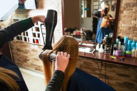 Making hairstyle using hair dryer