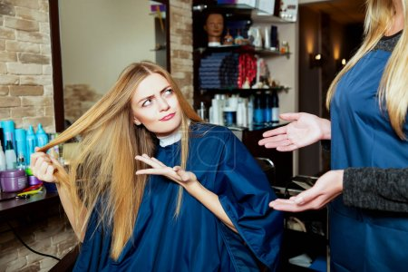 Beautiful woman showing hair to hairdresser