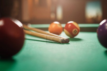 Billiard balls and cues on green cloth of pool tab...