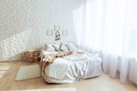 Photo for Light bedroom interior with big bed and white brickwall - Royalty Free Image
