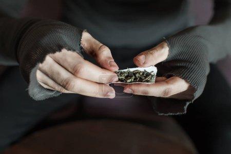 Photo pour ADDICT des mains faisant la marijuana jambage closeup, fond en bois - image libre de droit