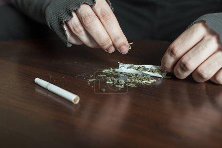 Photo pour ADDICT des mains faisant la marijuana jambage closeup, fond en bois. - image libre de droit