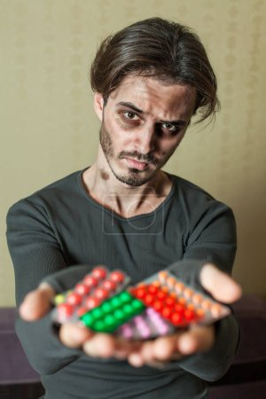 Drugs addict is holding tablets
