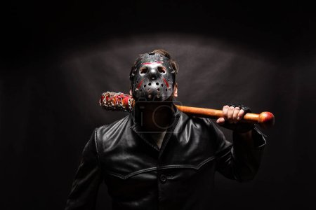 Photo for Bloody maniac in hockey mask and black leather coat with bat on black background - Royalty Free Image