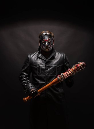 Photo for Bloody maniac in hockey mask and black leather coat with bat on black background. - Royalty Free Image