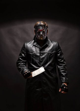 Portrait of bloody murderer in hockey mask holding...