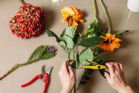 female florist cutting flower stalk