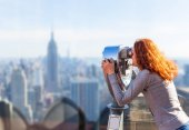woman looking at city through observation binoculars