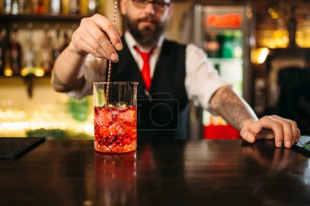 Photo for Bartender mixing red cockltail at bar counter - Royalty Free Image