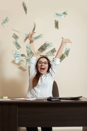 Photo for Smiling young female accountant throwing up dollars and making money rain - Royalty Free Image