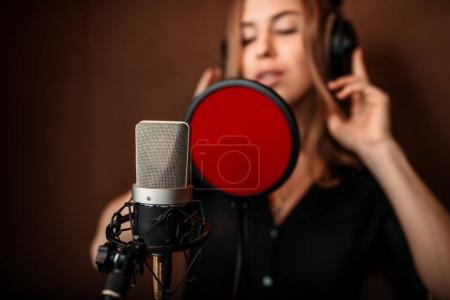 Photo pour Chanteuse enregistrant une chanson en studio de musique. Chanteuse avec écouteurs contre microphone. Enregistrement audio. Technologies sonores numériques professionnelles - image libre de droit
