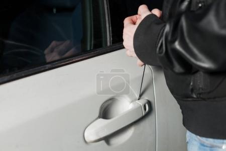 Photo pour Voleur de mâle essayant d'ouvrir la portière de voiture avec le tournevis. CarJacker véhicule Debloquer - image libre de droit