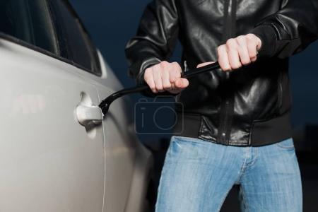 Photo pour Voleur de mâle essayant d'ouvrir la portière de voiture avec pied de biche. CarJacker véhicule Debloquer - image libre de droit
