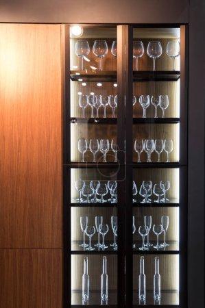 Photo pour Armoire en bois avec des lunettes, décoration d'intérieur plat. Meubles de cuisine, restaurant ou bar - image libre de droit