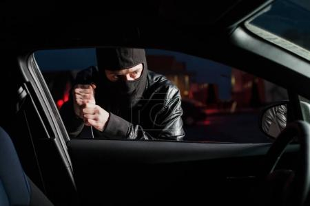Male thief  in balaclava trying to open car door w...