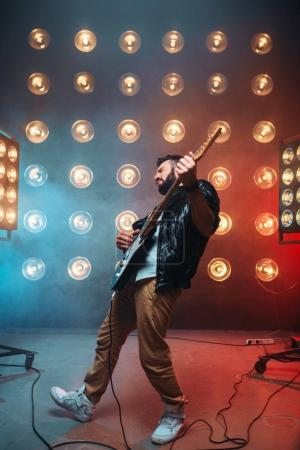 Photo for Male bearded guitarist with electric guitar on the stage with the decorations of lights - Royalty Free Image