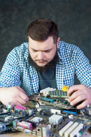 Service engineer working with computer motherboard
