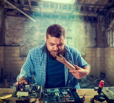 Photo for Male engineer fixing problem with computer hardware. Electronic device repair technology - Royalty Free Image
