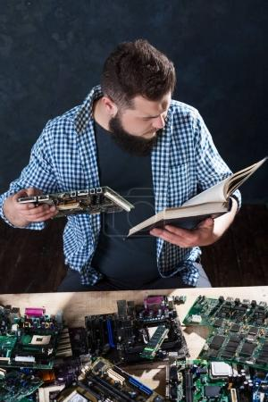 Photo for Male engineer fixing problem with computer hardware and reading professional reference book. Electronic device repair technology - Royalty Free Image