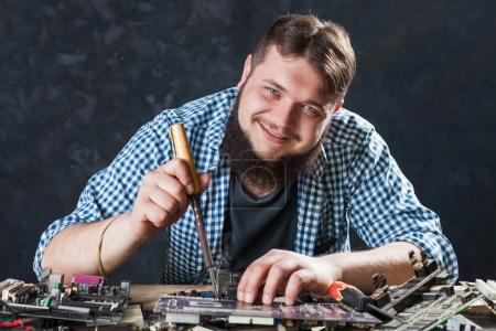 Photo for Service engineer repairing computer components with soldering iron. Repairman fixing problem with soldering tool - Royalty Free Image