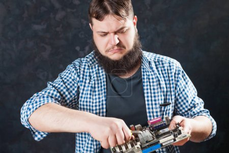 Photo for Service engineer repairing pc motherboard. Repairman making electronic components diagnostic - Royalty Free Image