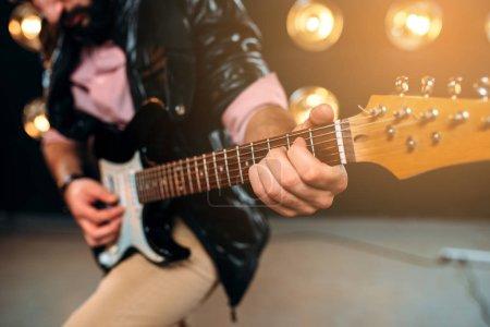 Photo pour Recadrée photo du guitariste mâle avec guitare électrique sur la scène - image libre de droit