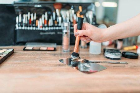Photo pour Main de maquilleuse avec pinceau préparant des cosmétiques, studio de beauté sur fond. Maquillage professionnel - image libre de droit
