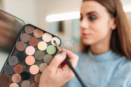 Photo pour Professionnel maquilleur tenant palette de fard à paupières et travaillant avec le visage de belles clientes dans le salon de beauté - image libre de droit