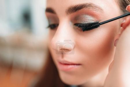 Photo pour Maquilleur professionnel mettre de mascara sur les cils des clientes dans le salon de beauté - image libre de droit