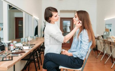 Photo pour Maquilleur professionnel travaillant avec le visage de belles clientes dans le salon de beauté - image libre de droit