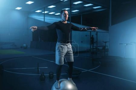 Photo for Athletic man training in gym, balance workout with bouncy ball in gym - Royalty Free Image