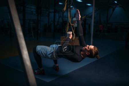 Photo for Athletic man training in gym, stretch endurance workout with ropes in gym - Royalty Free Image