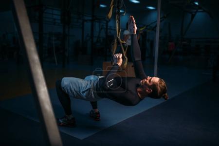 Photo pour Homme athlétique formation en salle de gym, entraînement endurance extensible avec des cordes dans la salle de gym - image libre de droit