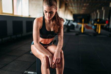 Photo pour Athlète féminine au repos après une formation en salle de sport. Slim femme assise sur le banc en club de remise en forme - image libre de droit