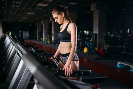 Photo pour Jeune femme sportive en cours d'exécution sur le tapis roulant dans la salle de gym - image libre de droit
