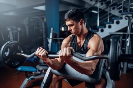 muscular athlete training with barbell