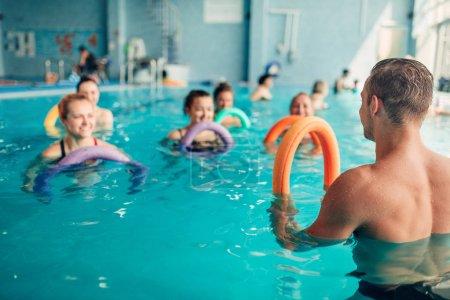 Photo pour Entraînement d'aérobic aquatique avec équipement lumineux dans le centre de sports nautiques, piscine intérieure, loisirs récréatifs - image libre de droit