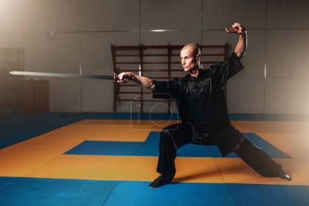 Photo for Masculine wushu fighter in black clothes training with sword, martial arts concept - Royalty Free Image